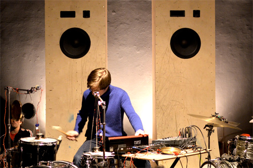 Ein Musiker in einem lila Hemd. Er bedient ein Mischpult und spielt Schlagzeug.