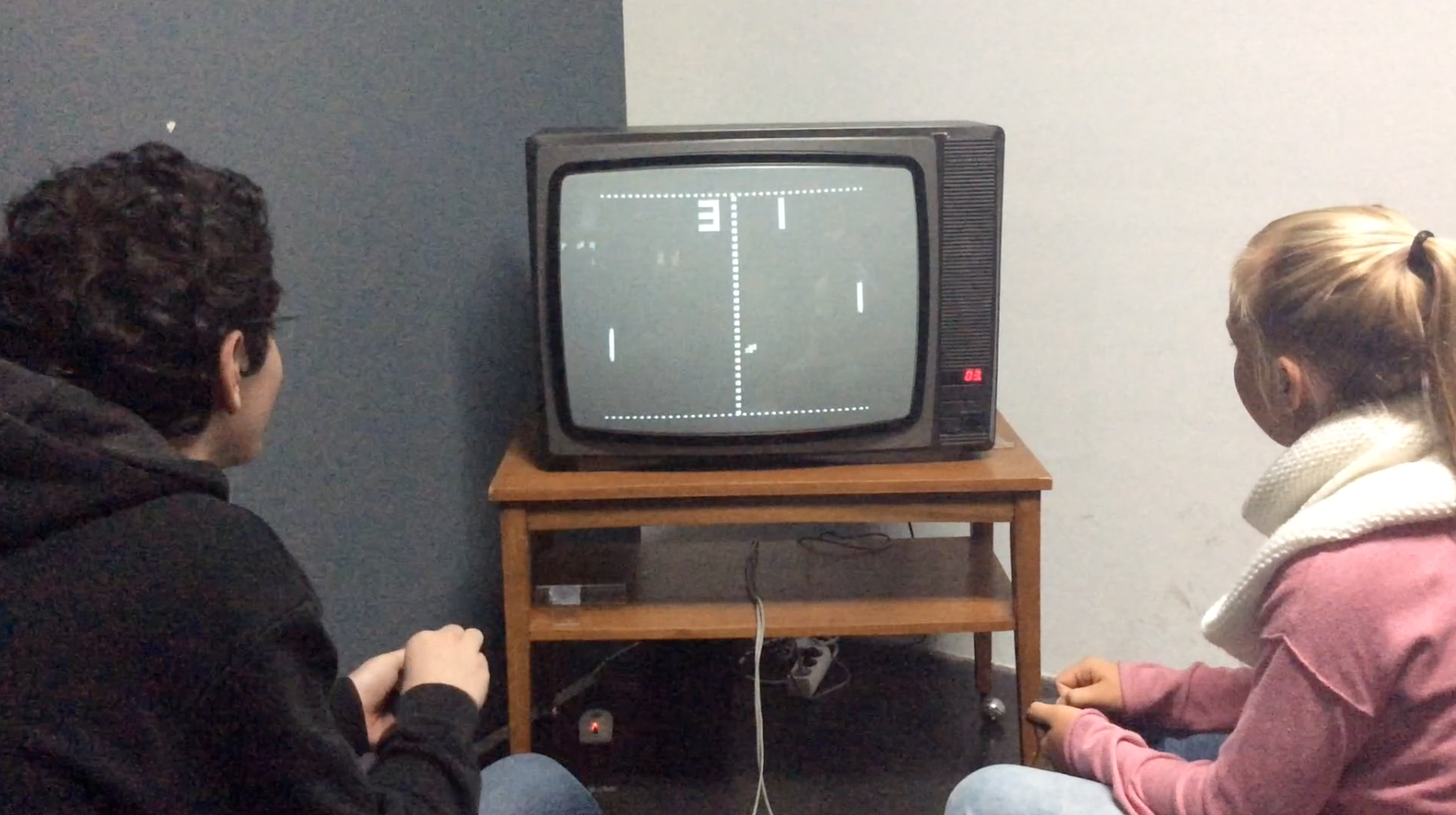 A boy and a girl sitting in front of an old tube TV and play Ping Pong
