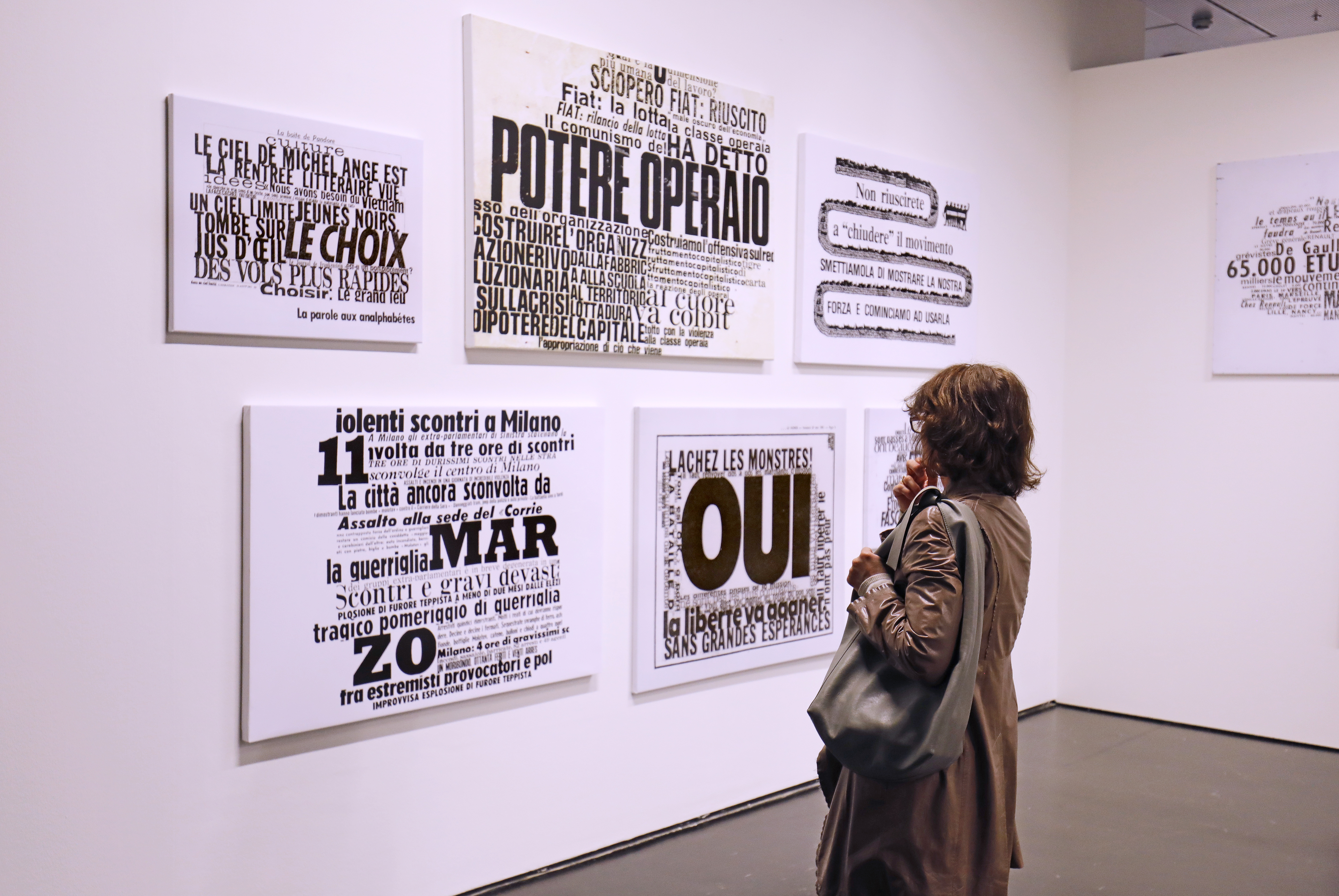 The picture shows the back of a woman looking at the collages of the artist Nanni Balestrini.