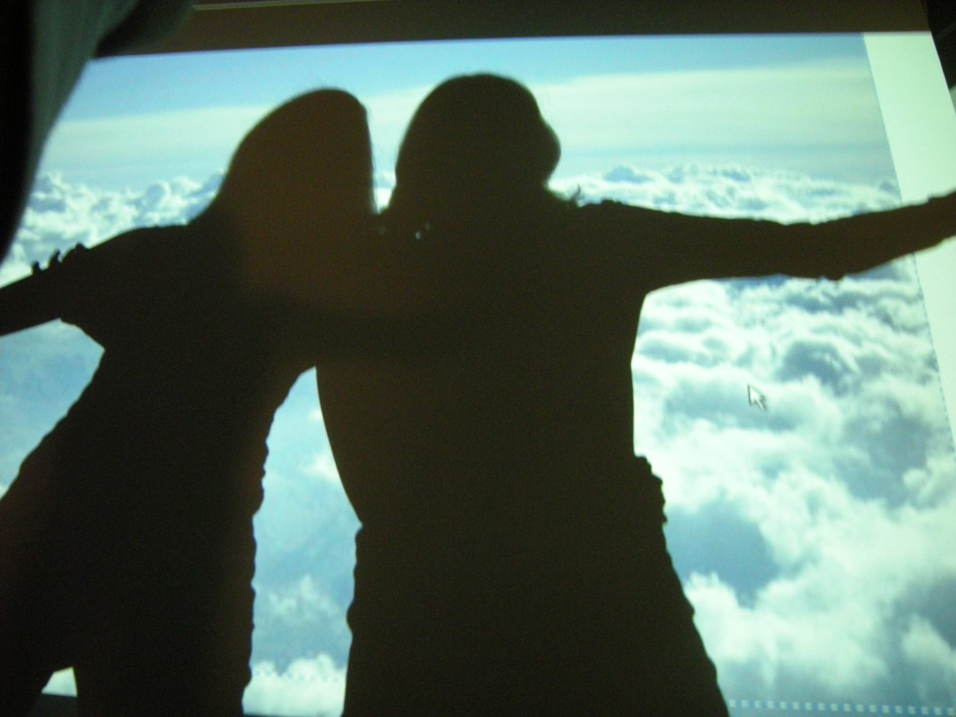 On a screen shadows of two people hugging and spreading their arms are casted. On the screen is a blanket of clouds projected.