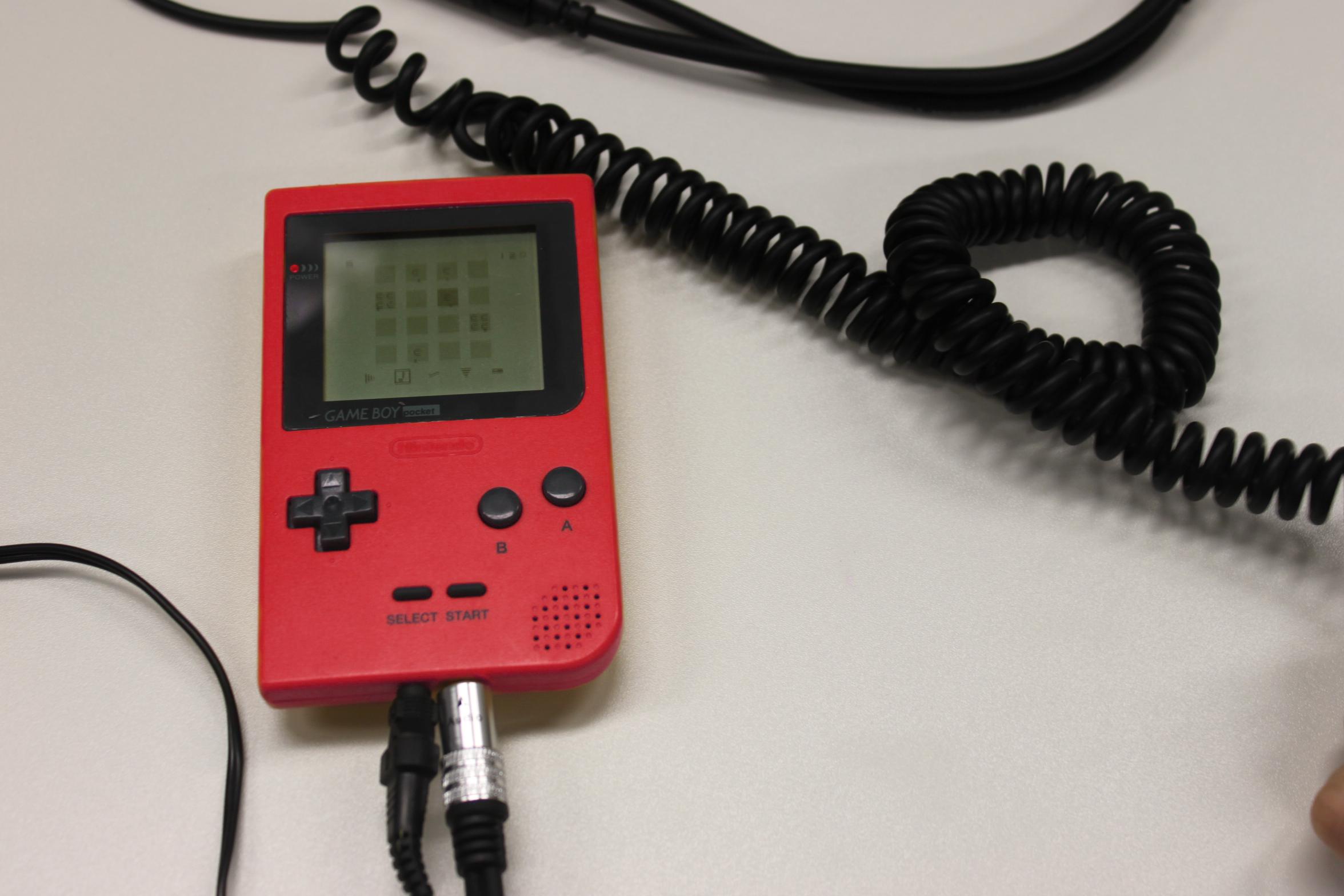Ein roter Gameboy liegt auf dem Tisch, darum einige Kabel.