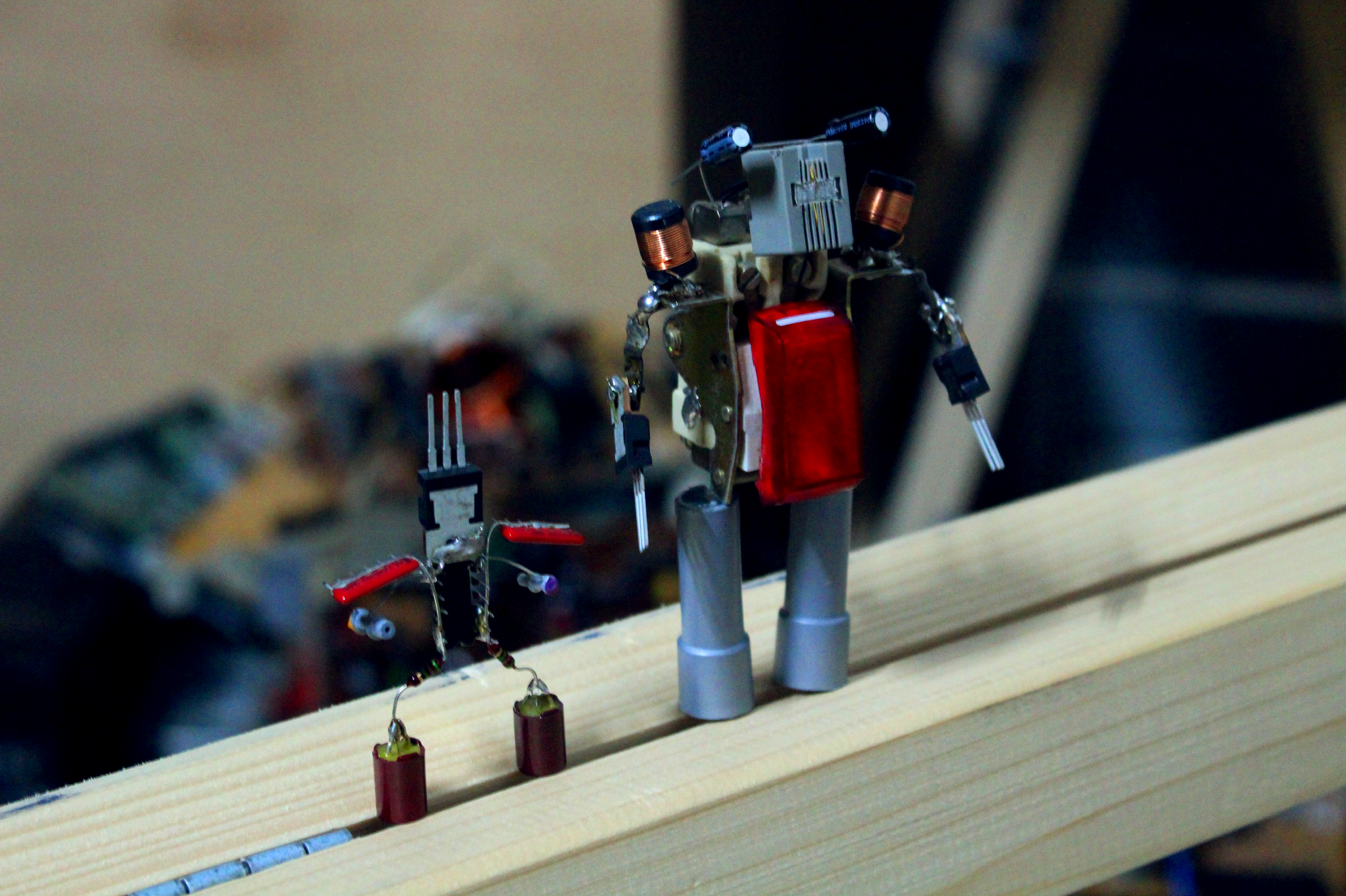 On a timber there are standing two little robots that are soldered together out of electronic scrap.