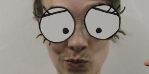 Eine junge Frau schaut verschmitzt mit gekräuselten Lippen in die Kamera. Ihre großen comic-artigen Augen sind auf eine Folie aufgezeichnet, die sie vor ihr Gesicht hält.