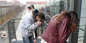 Drei Jugendliche fotografieren vor dem ZKM auf der Außentreppe am Kubus in verschiedene Richtungen
