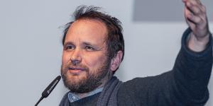The photo shows Tomás Saraceno during his presentation at the Frei Otto Symposium.
