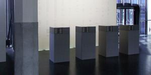 Four gray filing cabinets in front of a brightly lit wall.