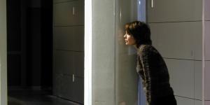 Woman presses her ear against a plexiglas loud-speaker installed on a column
