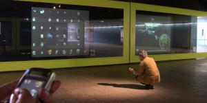 Auf die Glaswände des Ausstellungsraums ZKMax wird »SpacePlace« projiziert. Davor sieht man Personen mit Mobiltelephonen, die mit der Installation kommunizieren.