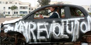 "A woman sitting in a non-functioning car. On the driver's side was sprayed with white color ""revolution""."