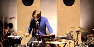 A musician in a purple shirt. He uses a mixer and plays drums.