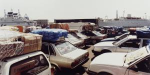 Fotografie mehrerer geparkter Autos, alle voll beladen. Im Bildhintergrund sind zwei große Kreuzfahrtschiffe.