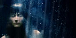 A woman looks through a with rain blurred window
