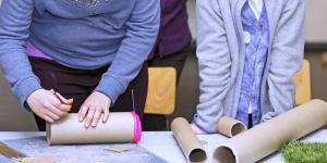 Two girls are standing in front of a table with cardboard-rolls. One of them is marking the roll in front of her with a pencil.