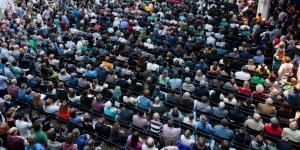 Vor einer Bühne, auf der ein Mann referiert, sitzen viele Menschen auf Stühlen