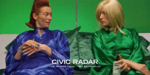 Eine Frau in zwei verschiedenen Aussehen. Auf der linken Seite im blauen Seidenmantel und braunen Haaren, auf der rechten Seite im grünen Seidenmantel und blonden Haaren. Beide sitzen nebeneinander und schauen sich an.