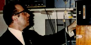 A man in a black suit and black horn-rimmed glasses served various electronic equipment.
