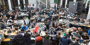Eine Raum voller Menschen, die an Tischen vor ihren PCs sitzen