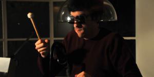 Ein Mann mit Sonnenbrille und durchsichtigem Lampenschirm auf dem Kopf, der einen Drumstick in seiner rechten Hand hält.