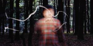 A blurry man standing in the forest