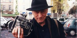 Jonas Mekas mit einem Hut auf dem Kopf und einer Kamera in der Hand