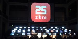 Monitore und dahinter in großen, weißen Buchstaben auf rotem Hintergrund: 25 zkm