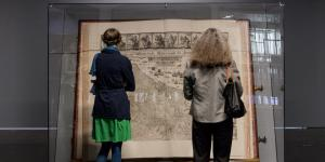 The Klencke Atlas (1660) is one of the largest atlas in the world. Aerated he stands in a glass structure that protects it. Two women seen from behind looking at it.