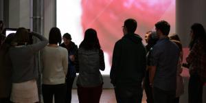 Eine Gruppe von Menschen vor einer Kunstvermittlerin. Im Hintergrund ist großflächig ein Teil einer Zunge zu sehen.