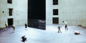 Sieben Tänzer bewegen sich um eine große rechteckige schwarze Wand, die einen Bühnenraum strukturiert.
