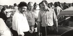 Three man standing around a car