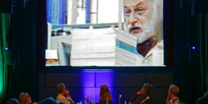 The members of the panel are looking at the projection screen above their head displaying a video with Vilém Flusser