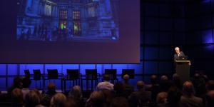 Ein Mann steht hinter einem Podium und hält einen Vortrag.