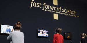 Drei Menschen mit Kopfhörern auf den Ohren schauen verschiedene Videos des »fast forward science 2015« Wettbewerbs an.