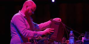 Ein Mann mit langem Bart steht vor einem Koffer mit vielen Kabeln