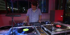 Ein Mann mit Kopfhörern vor einem DJ-Set