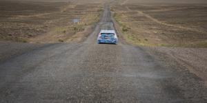 A blue car driving through a desert landscapes
