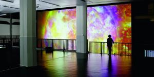 Riesige Leinwand aus feuerfarbener Datenmatrix, davor eine Frau am Geländer