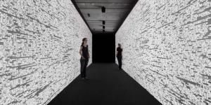 Two women in a corridor. The walls are made out of numbers.