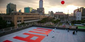"""Das Wort """"Many"""" in roten Buchstaben auf einem Dach"""