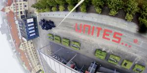 """Das Worte """"unites"""" in roten Buchstaben auf dem ZKM_Vorplatz"""