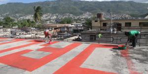 """Personen malen das Wort """"worlds"""" auf ein Dach"""
