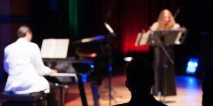Ein Mann in weißem Anzug am Klavier. Eine Frau im schwarzen Kleid spielt Geige.