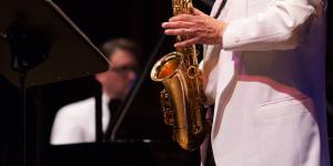 Ein Mann am Klavier, im Vordergrund ein Saxophon