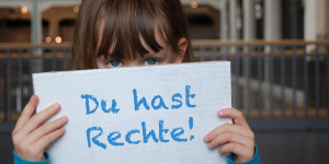 """A little girl holding a placard in front of her face: """"Du hast Rechte!"""""""