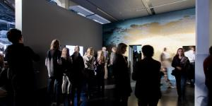 Many people standing in a room, looking at the artworks