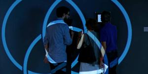 Three people standing in front of a wall. Blue circles are projected on them
