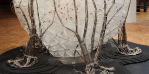 Weißer, organischer Körper aus einer Dreiecksstruktur, wird von mehreren Kabelsträngen getragen. Die Kabelführung ähnelt einem Geäst.