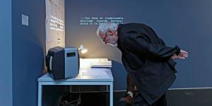 Ein Mann liest vor einem kleinen Bildschirm die Beschreibung