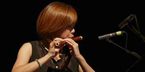A woman playing a kind of transverse flute