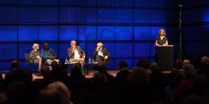Vier Personen sitzen auf einer Bühne. Eine weitere Person steht rechts von ihnen an einem Podest und spricht zu dem Publikum