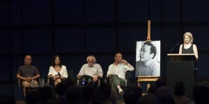 Vier Personen sitzen auf der Bühne. Am Rednerpult spricht eine Frau und ein großes schwarz-weiß Foto von einem jungen Mann ist aufgestellt.